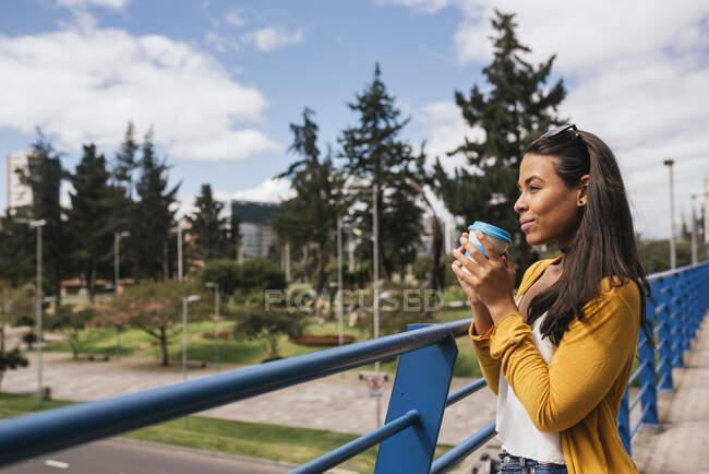 Mulher jovem e atenciosa segurando bebida olhando para longe enquanto estava de pé por trilhos na passarela — Fotografia de Stock