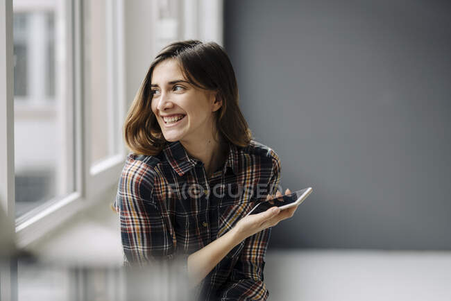 Portrait of laughing young woman with smartphone looking out of window — Stock Photo