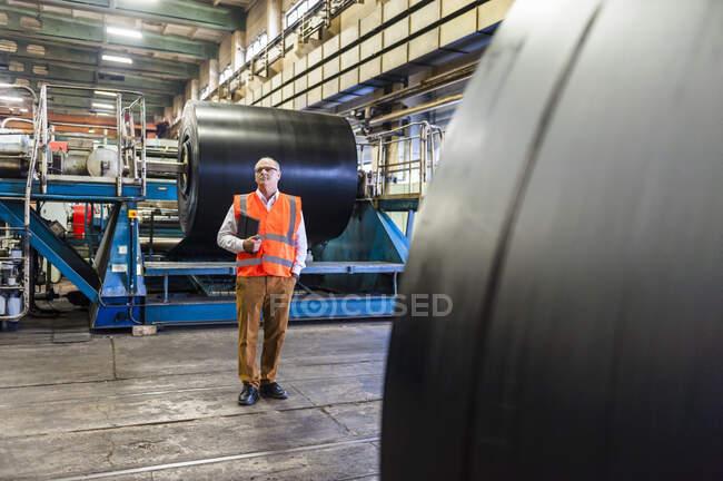 Homem sênior vestindo colete de segurança em uma fábrica de processamento de borracha — Fotografia de Stock