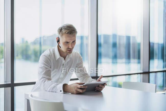 Empresario haciendo una llamada con auriculares, usando tableta digital - foto de stock