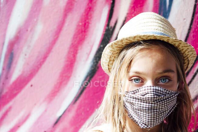 Retrato de cerca de la niña que usa mascarilla y sombrero contra la pared rosa - foto de stock