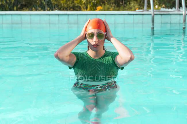 Retrato de mujer en piscina con gorra roja, jersey de punto verde y gafas de sol - foto de stock