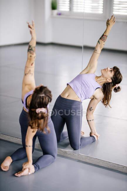 Артистка балета делает упражнения на растяжку перед зеркалом в студии — стоковое фото