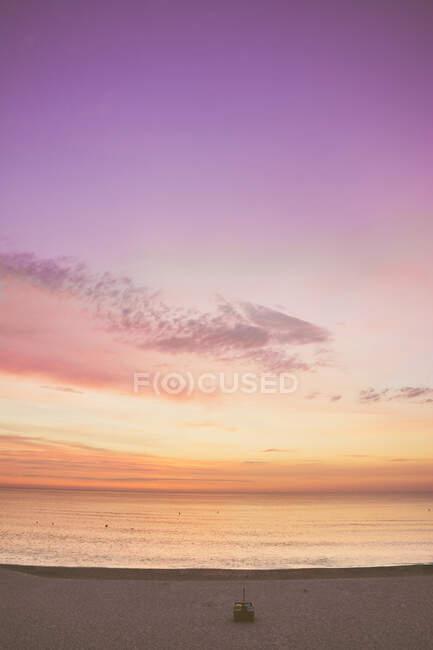 Vista panorámica del cielo púrpura y naranja sobre el mar durante el amanecer - foto de stock