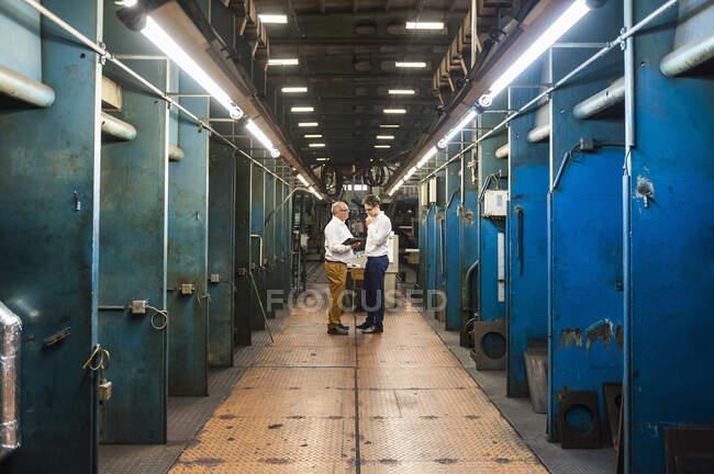 Dois empresários que têm uma reunião em um salão de fábrica — Fotografia de Stock