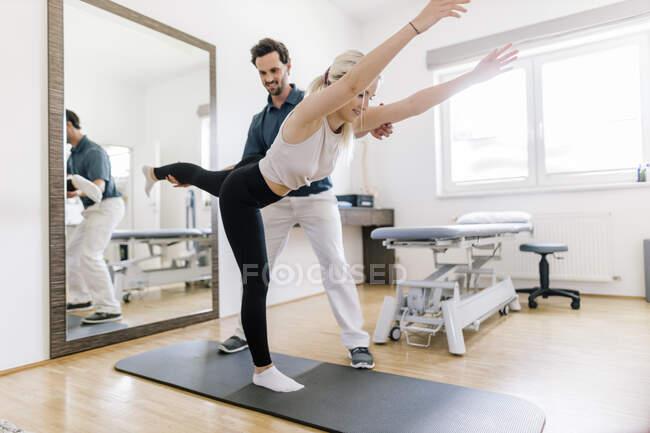 Fisioterapeuta assistindo paciente do sexo feminino, equilibrando no tapete ginásio — Fotografia de Stock