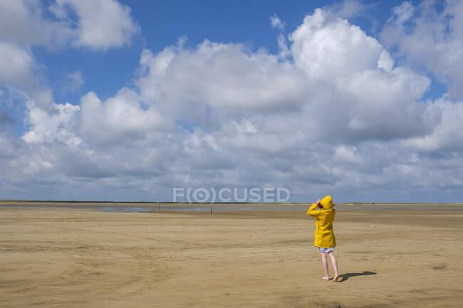 Vista trasera de longitud completa de la adolescente con impermeable amarillo mientras camina sobre la arena en la playa durante el día soleado - foto de stock