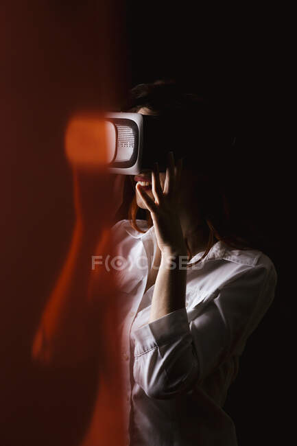 Young woman wearing VR glasses against black background — Stock Photo