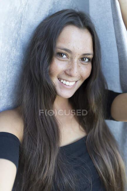 Ritratto ravvicinato di giovane donna sorridente lentigginosa contro la tenda a casa — Foto stock