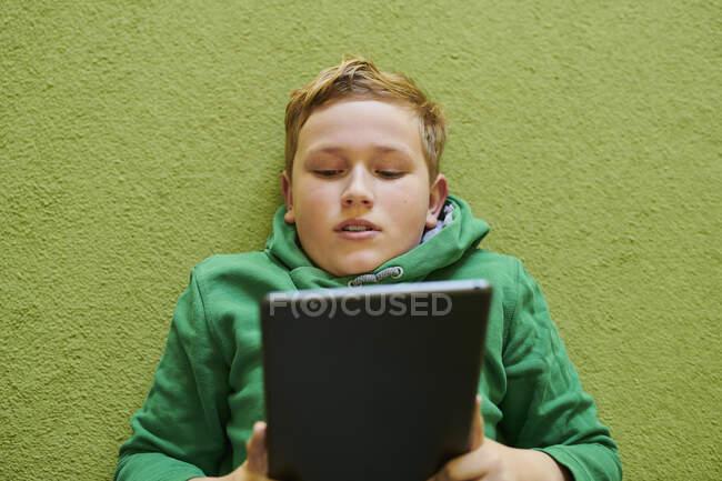 Мальчик, использующий цифровой планшет на зеленом ковре дома — стоковое фото