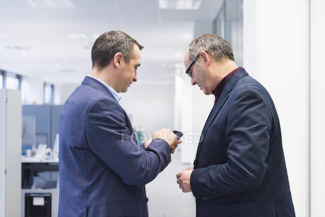 Dos hombres de negocios compartiendo teléfono inteligente en la oficina - foto de stock