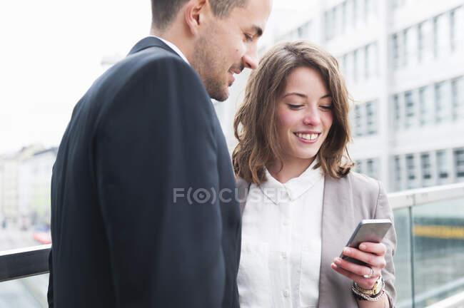 Casal de negócios usando telefone inteligente fora do prédio de escritórios — Fotografia de Stock