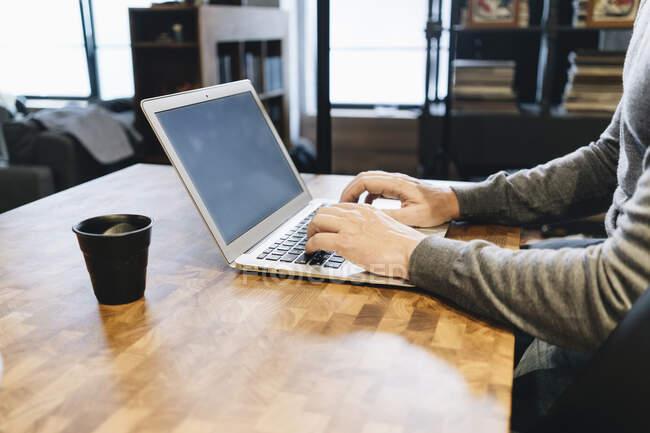 Зрілий бізнесмен працює на кухні, використовуючи ноутбук. — стокове фото