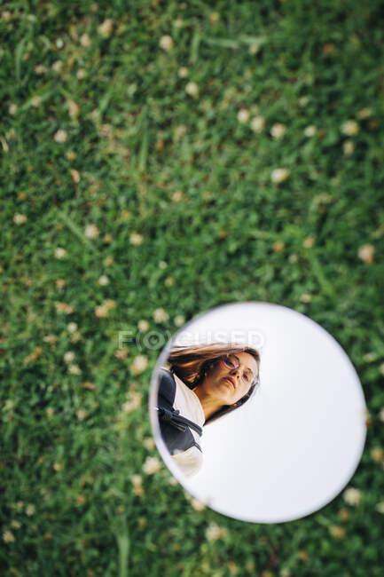 Красивая женщина, отражающаяся на зеркале над травянистой землей в парке — стоковое фото