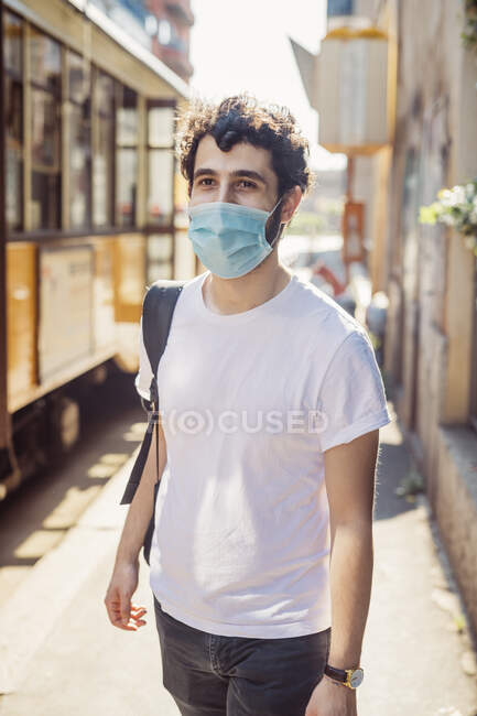 Jovem usando máscara andando na rua da cidade durante o dia ensolarado — Fotografia de Stock