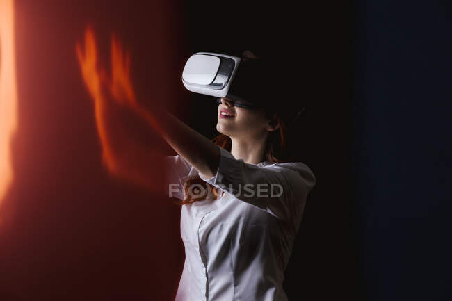Young woman gesturing while using VR glasses over black background — Stock Photo