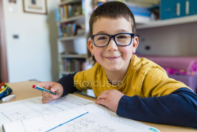 Smiling cute boy sitting with book at desk during COVID-19 homeschooling — Stock Photo