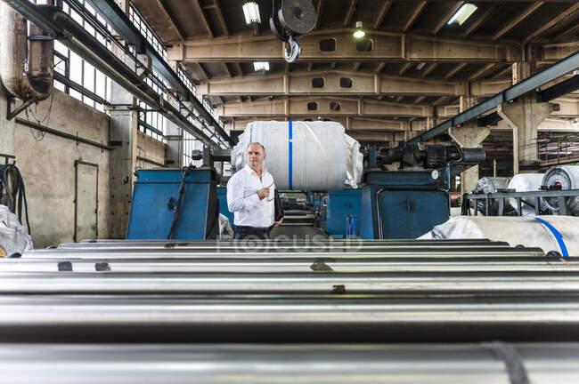 Старший бізнесмен у заводському залі. — стокове фото