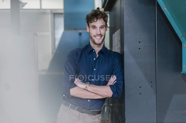 Portrait of a smiling young businessman in a factory — Stock Photo