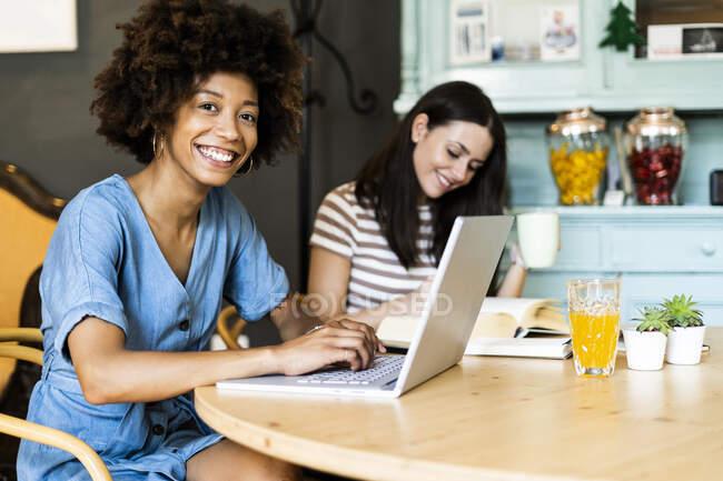 Amigos femininos felizes estudando com laptop no café — Fotografia de Stock