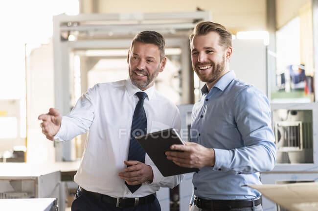 Deux hommes d'affaires souriants avec tablette ayant une réunion dans une usine — Photo de stock