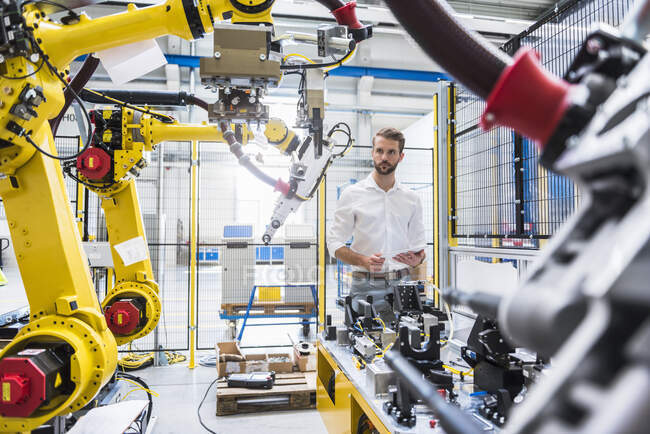 Confident robotics expert looking at machinery in manufacturing factory — Stock Photo