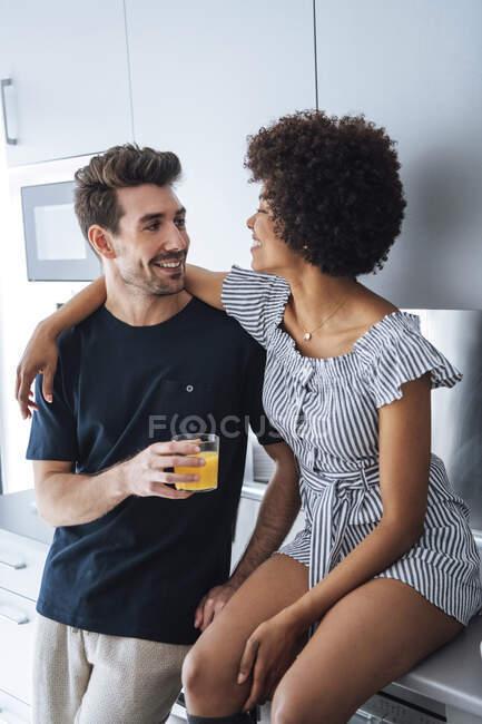 Ласковая многонациональная пара на кухне пентхауса — стоковое фото