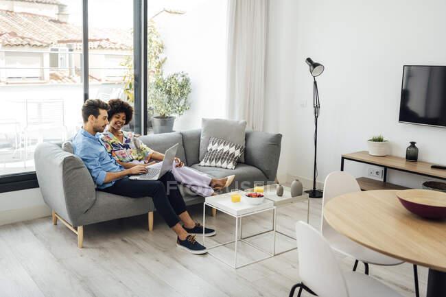 Багатоетнічна пара використовує ноутбук, сидячи на дивані в сучасному пентхаусі. — стокове фото