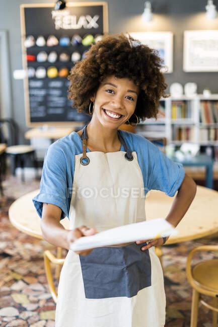 Щаслива господиня тримає меню, стоячи з рукою на стегні в кав