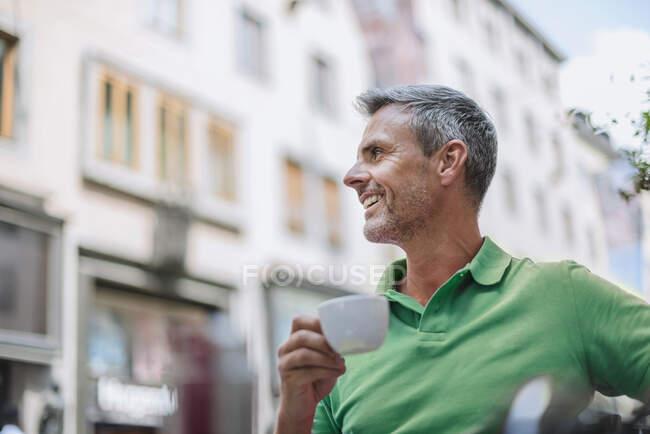 Sorrindo homem maduro segurando xícara de café olhando para longe enquanto sentado no café calçada — Fotografia de Stock