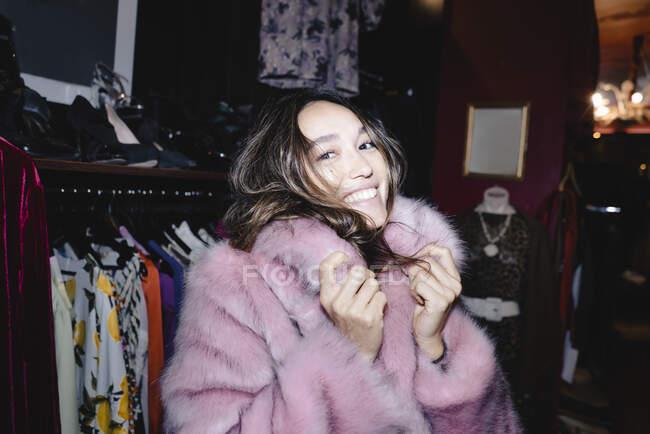 Портрет усміхненої жінки у рожевій куртці для хутра в магазині. — стокове фото