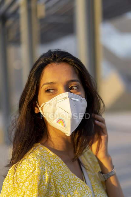 Mujer joven reflexiva con máscara facial en la ciudad - foto de stock