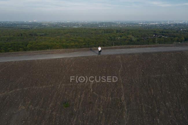 Empresário em pé na colina contra o céu, vista drone — Fotografia de Stock