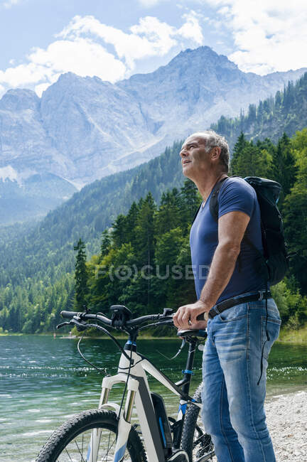 Senior man with e-bike at Eibsee lakeside — Stock Photo