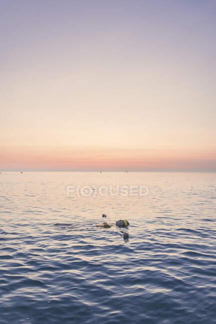 Ragazza adolescente che nuota in mare contro il cielo durante l'alba — Foto stock