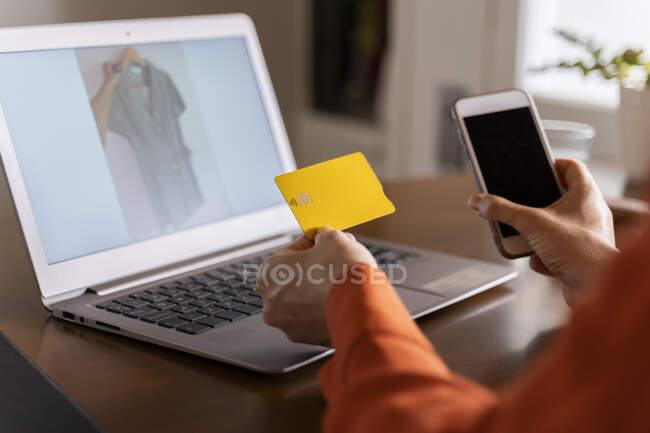 Image recadrée de femme d'affaires avec carte de crédit en utilisant un téléphone intelligent lors de l'achat en ligne à la maison — Photo de stock