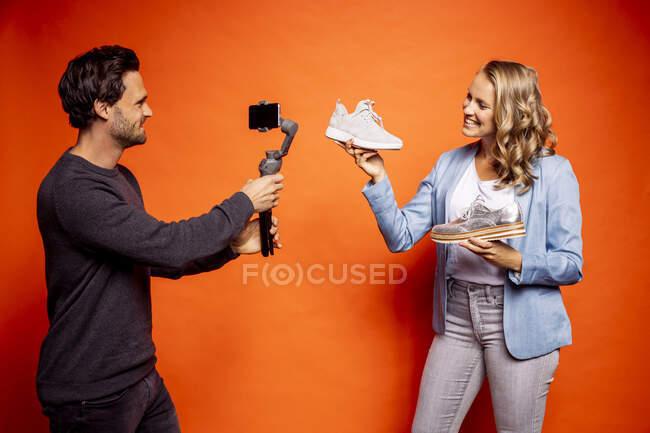 Sorrindo mulher mostrando sapatos enquanto homem fotografando-a através de telefone inteligente contra fundo laranja — Fotografia de Stock