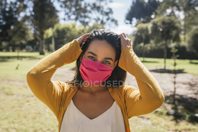 Close-up of young woman wearing mask standing in park during sunny day — Stock Photo