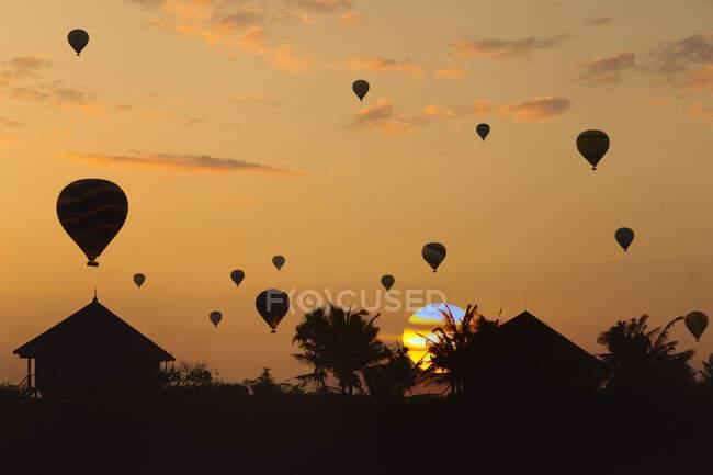 Indonesia, Bali, Siluetas de globos aerostáticos volando sobre cabañas costeras al atardecer - foto de stock