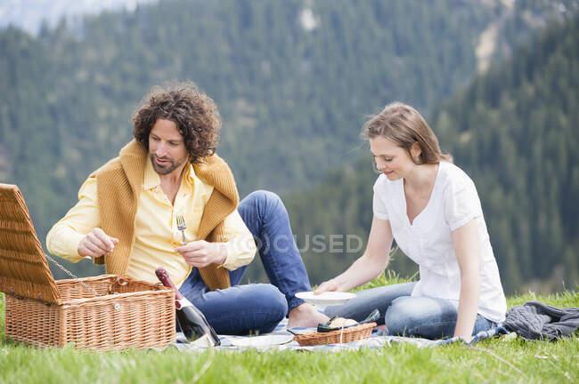 Mid adult couple enjoying picnic against mountain — Stock Photo