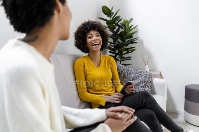 Портрет смеющейся девушки, сидящей на диване со своей подругой — стоковое фото