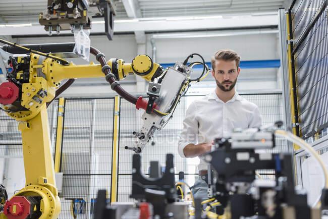 Especialista em robótica masculina confiante olhando para máquinas na indústria automatizada — Fotografia de Stock