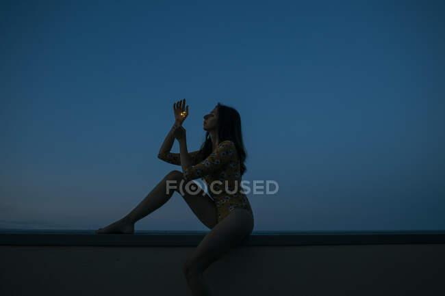 Vista lateral de la mujer sosteniendo chispeante mientras está sentada en la pared de contención contra el cielo azul claro durante la puesta del sol - foto de stock