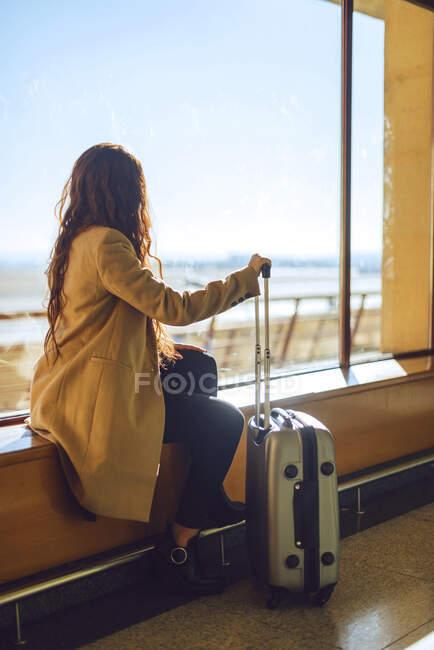 Empresaria sosteniendo equipaje de ruedas mientras está sentada en el alféizar de la ventana en el área de salida del aeropuerto - foto de stock