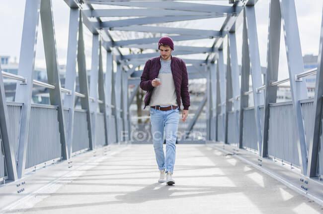 Jovem caminhando em uma ponte com fones de ouvido e smartphone — Fotografia de Stock