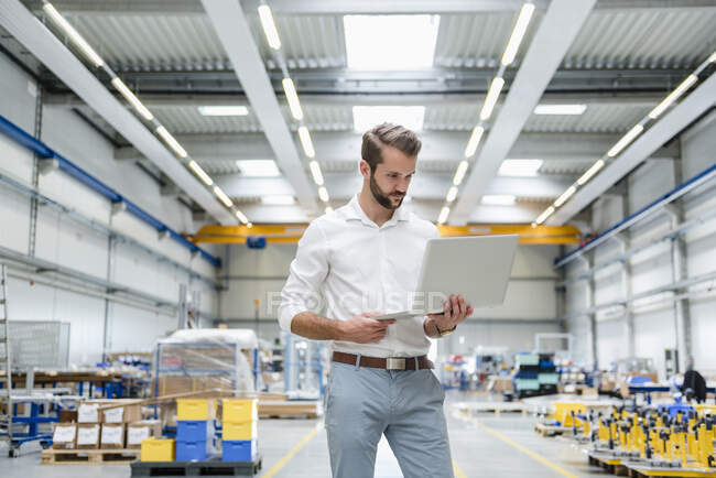 Young man using laptop on factory shop floor — Stock Photo