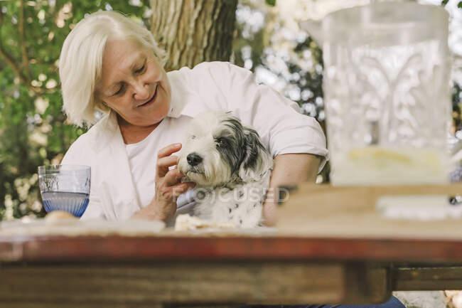 Sonriendo mujer mayor jugando con el perro mientras está sentado en la mesa en el patio - foto de stock