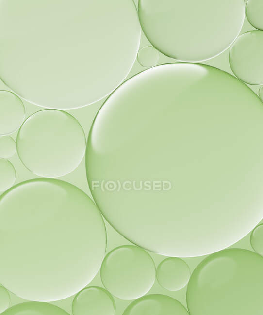 Three dimensional render of transparent glass spheres against green background — Stock Photo