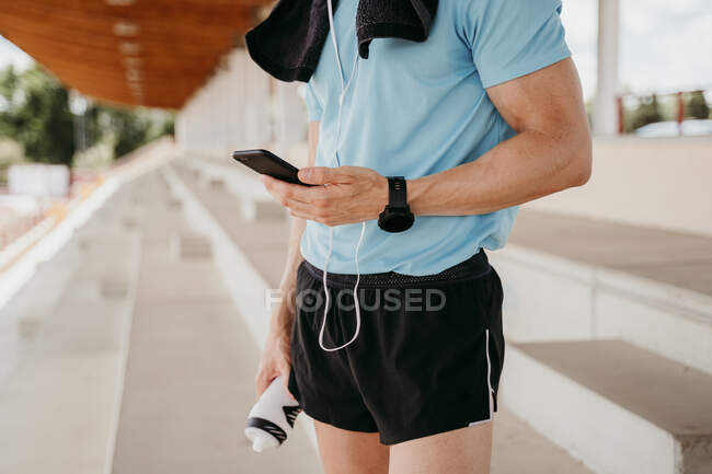 Male athlete checking smartphone on grandstand in stadium — Stock Photo