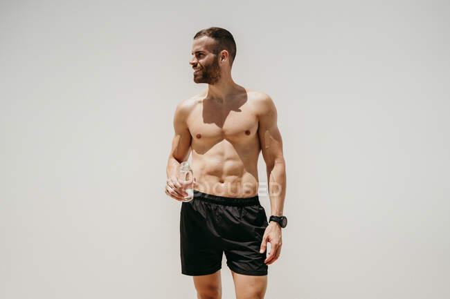 Спортсмен, що тримає пляшку води. — Stock Photo